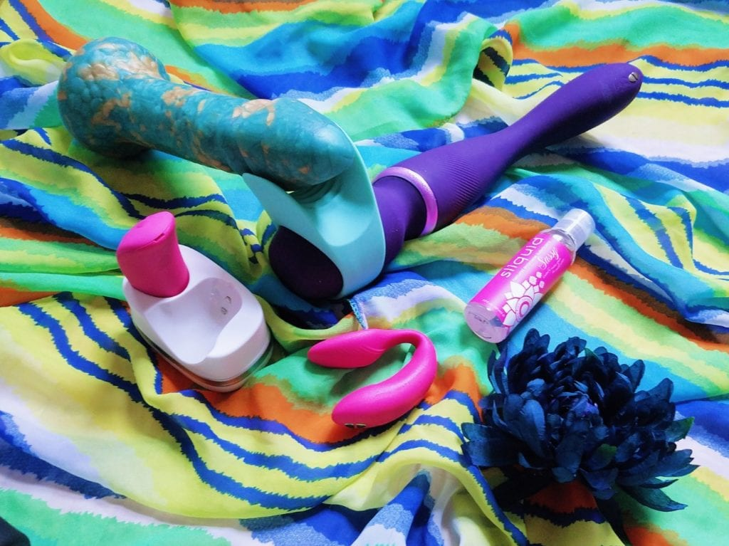 Image: We-Vibe Wand with stroker attachment, Uberrime Aqua-King dildo, We-Vibe Chorus couples' vibe, and Sliquid Sassy lubricant
