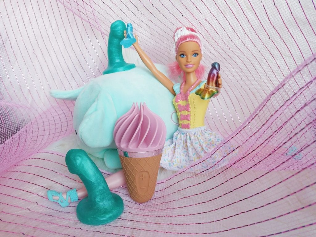 [Image: Barbie doll doing a split among Uberrime silicone teenie weenies, holding Barbie-sized dildos next to pink and brown Satisfyer Sweet Treat rotating ice cream clitoral stimulator]