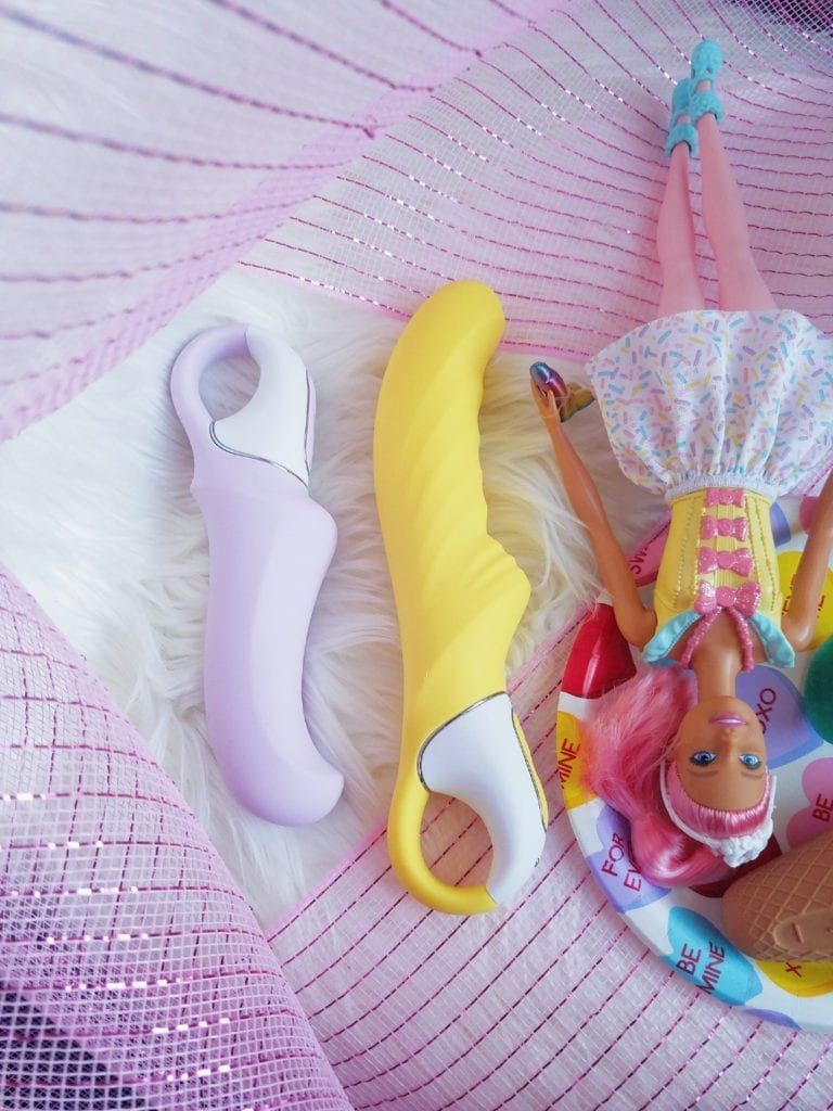 [Image: side view of the Satisfyer Charming Smile and Yummy Sunshine next to Barbie doll lying down]