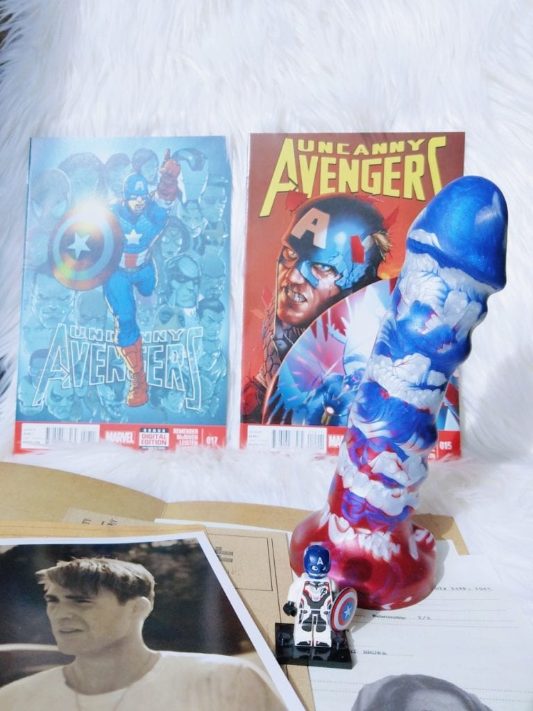 [Image: red, silver, and blue marbled silicone dildo with Avengers comic books, Captain America Lego minifigure, and photo of Steve Rogers before super-soldier treatment]