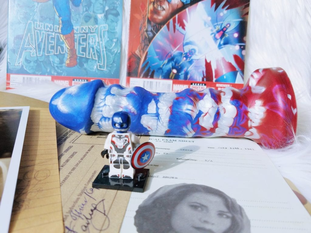 [Image: Uberrime A-Spot Avenger The Patriot Captain America-themed dildo between Avengers comic books, a Captain America Lego minifigure, and a photo of Peggy Carter]