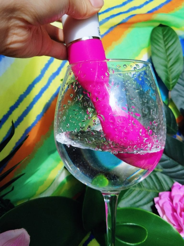 [Image: pink Xcitme Sym-B Luma rechargeable G-spot vibrator dipped in water and splashing]
