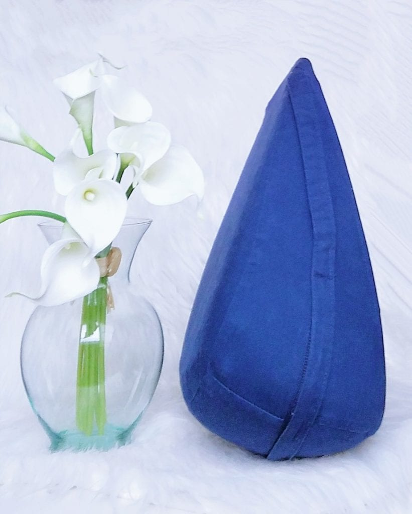 [Image: Dame Products Pillo indigo next to vase of faux white lilies]