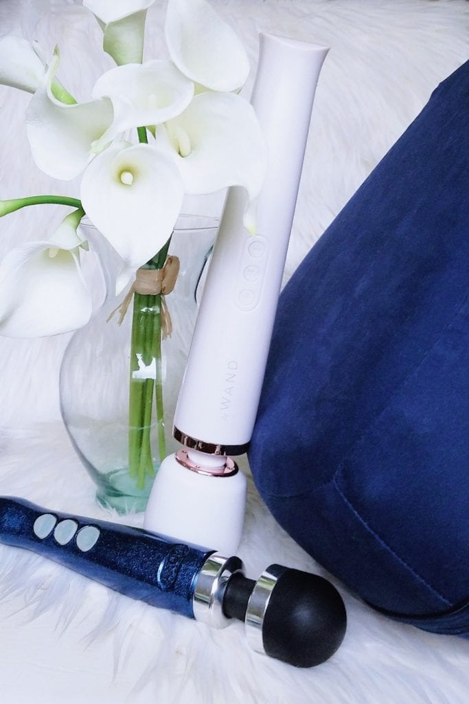 [Image: indigo Dame Pillo, vase of white lilies, white Le Wand Rechargeable, sparkly blue Doxy 3 Rechargeable]