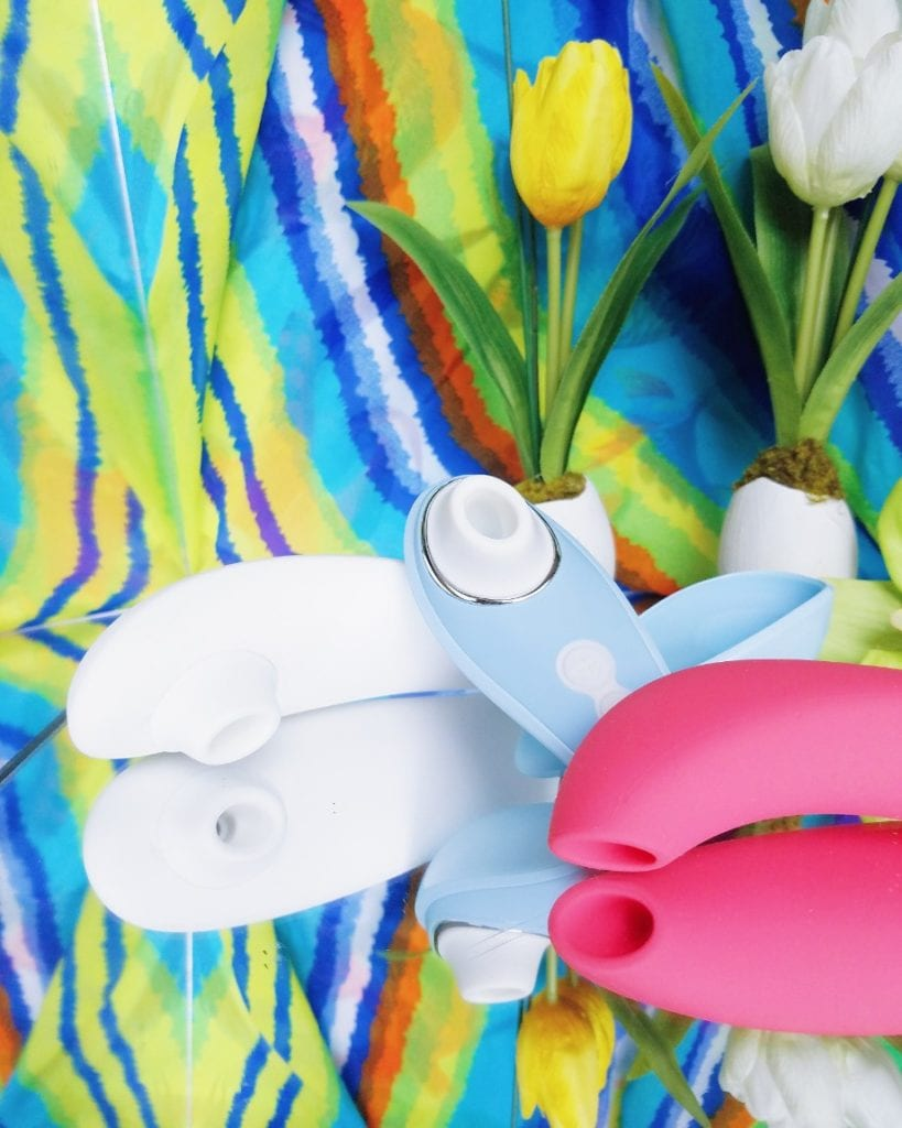 [Image: white Womanizer Premium, powder blue Womanizer Liberty travel-friendly clitoral suction toy, coral We-Vibe Melt]